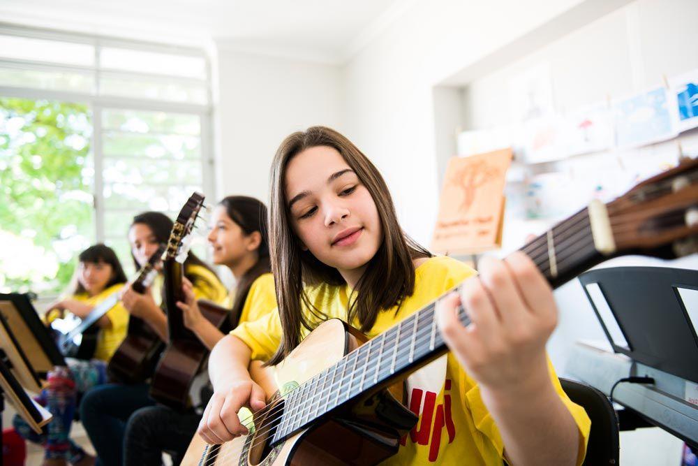 crianças do projeto Guri tocando instrumentos em sala de aula